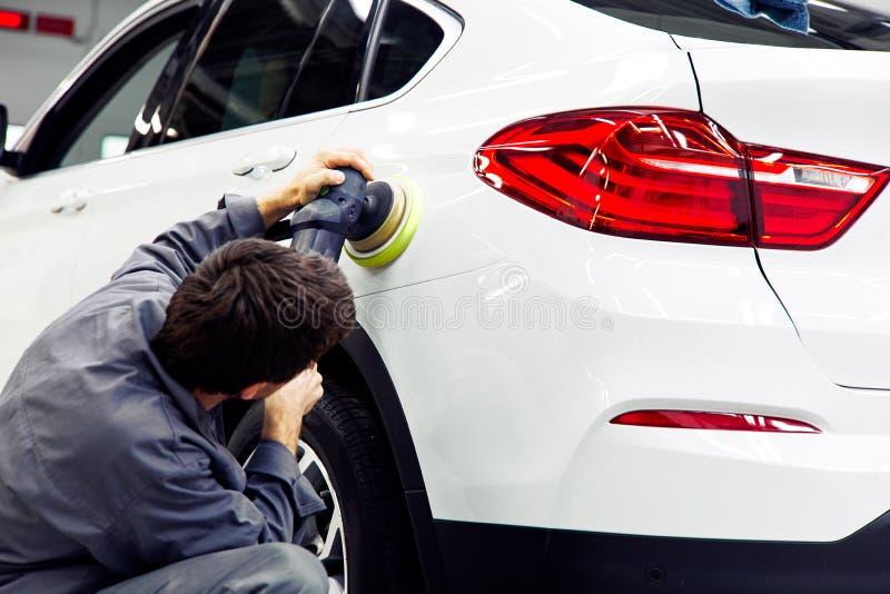 Detalle del coche - manos con el pulidor orbital en taller de reparaciones auto fotografía de archivo libre de regalías