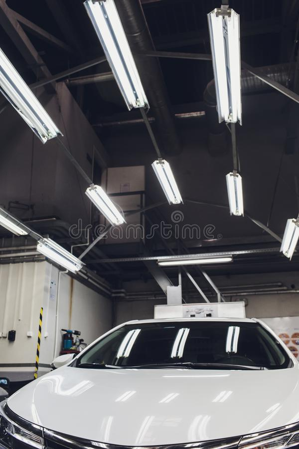 Detalle del coche - manos con el pulidor orbital en taller de reparaciones auto Foco selectivo foto de archivo libre de regalías