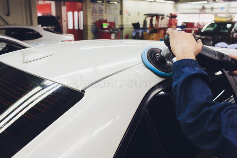 Detalle del coche - manos con el pulidor orbital en taller de reparaciones auto Foco selectivo imágenes de archivo libres de regalías