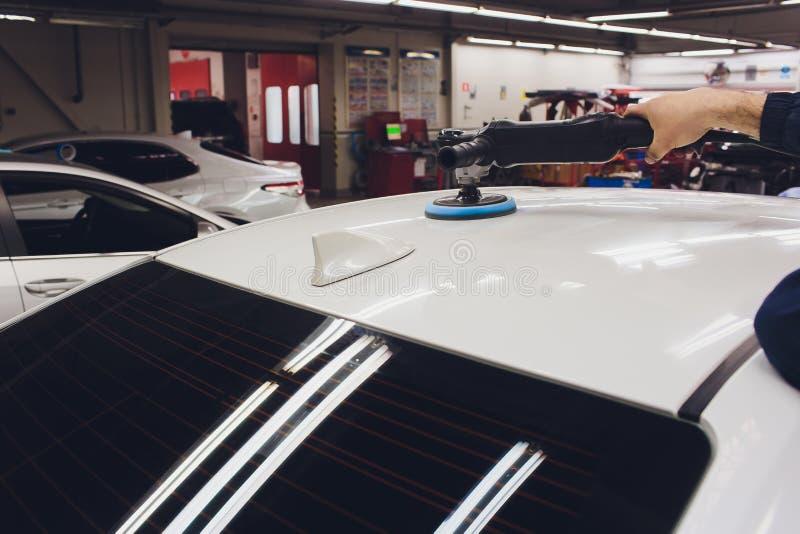Detalle del coche - manos con el pulidor orbital en taller de reparaciones auto Foco selectivo fotos de archivo libres de regalías