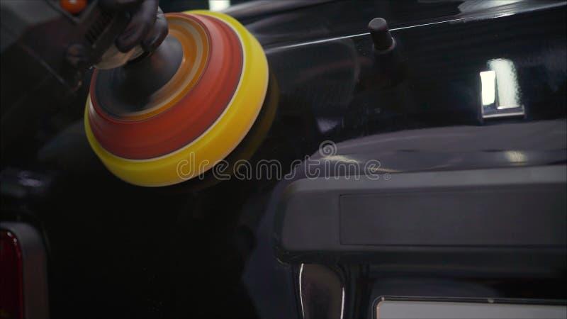 Detalle del coche - manos con el pulidor orbital en taller de reparaciones auto Foco selectivo Pulido del coche imagen de archivo