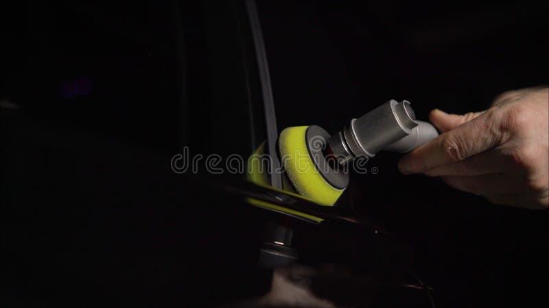 Detalle del coche - manos con el pulidor orbital en taller de reparaciones auto Foco selectivo Pulido del coche y corrección de L foto de archivo libre de regalías