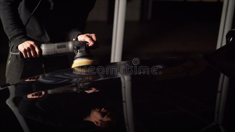 Detalle del coche - manos con el pulidor orbital en taller de reparaciones auto Coche negro pulido imagenes de archivo