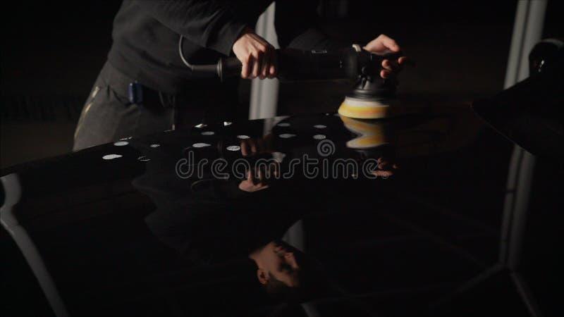 Detalle del coche - manos con el pulidor orbital en taller de reparaciones auto Coche negro pulido fotos de archivo