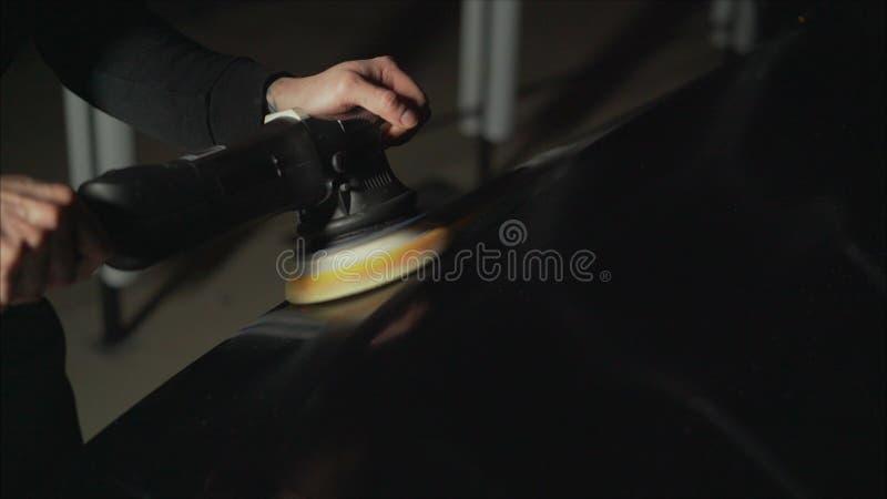 Detalle del coche - manos con el pulidor orbital en taller de reparaciones auto Coche negro pulido foto de archivo