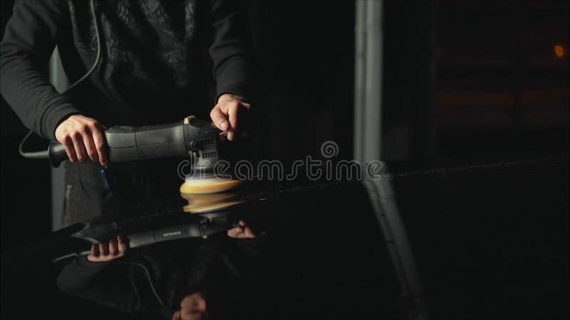 Detalle del coche - manos con el pulidor orbital en taller de reparaciones auto Coche negro pulido fotografía de archivo libre de regalías