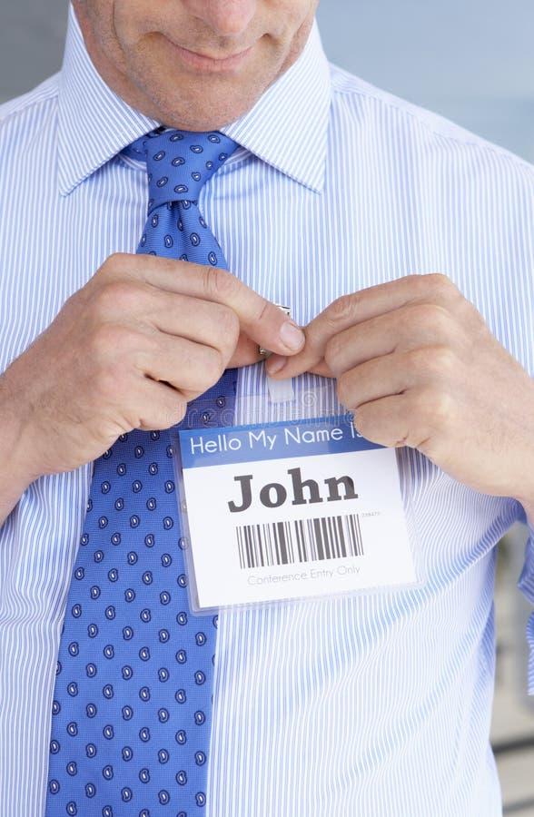 Detalle del delegado que fija en insignia de nombre en la conferencia imagen de archivo libre de regalías