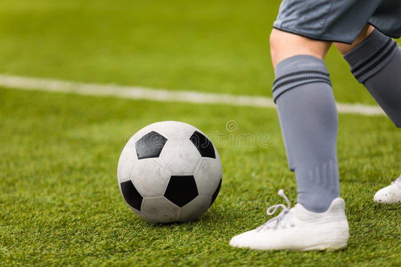 Detalle del fútbol Retroceso del balón de fútbol con el pie Pies del futbolista en la echada de la hierba foto de archivo
