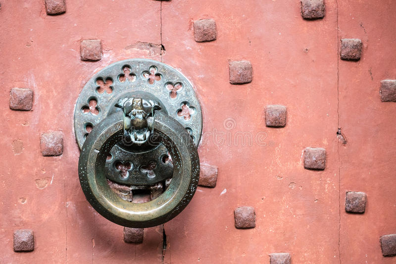 Detalle del golpeador de puerta de bronce antiguo en puerta roja vieja foto de archivo