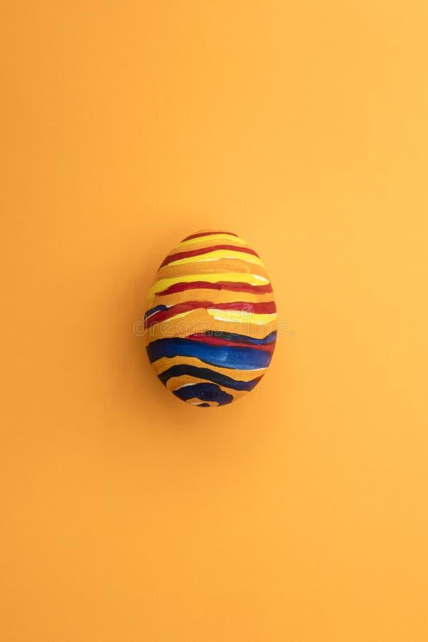 Detalle del huevo de Pascua amarillo pintado con las rayas rojas y azules en fondo anaranjado foto de archivo libre de regalías