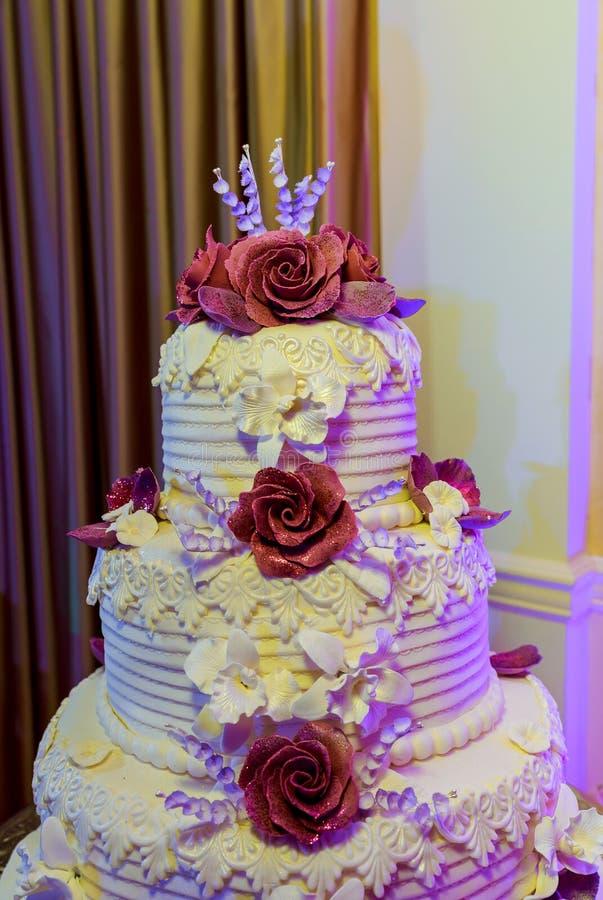 Detalle del pastel de bodas con las rosas rojas foto de archivo