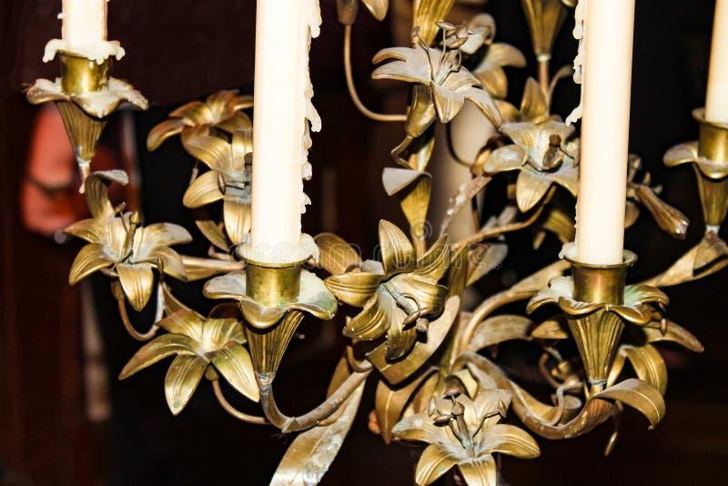 Detalle del primer de la lámpara de bronce vieja con las velas que gotean la cera fotos de archivo