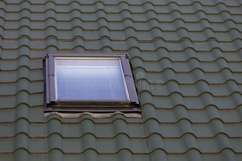 Detalle del primer de la ventana plástica del nuevo pequeño ático instalada en fondo escalonado verde oscuro del tejado de la cas fotografía de archivo