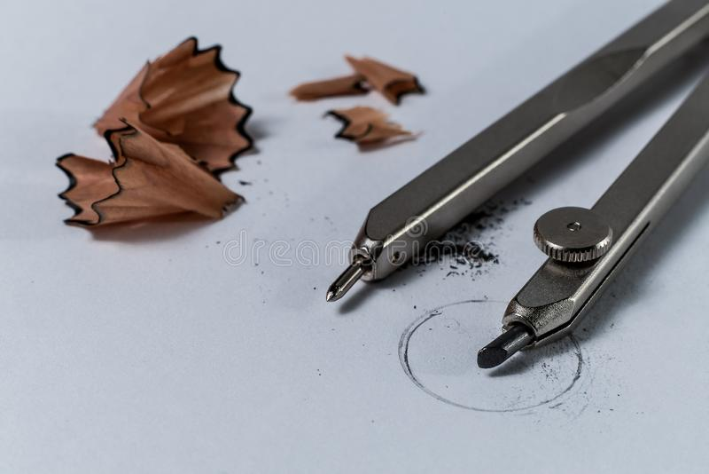 Detalle del primer de un compás del lápiz de la geometría y de un lápiz que afilan virutas de madera en el Libro Blanco con un cí foto de archivo libre de regalías