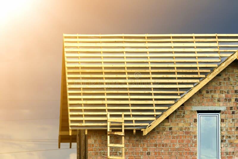 Detalle del primer del nuevo top de la casa del ladrillo con dos ventanas plásticas estrechas del ático y del bastidor de madera  imagenes de archivo