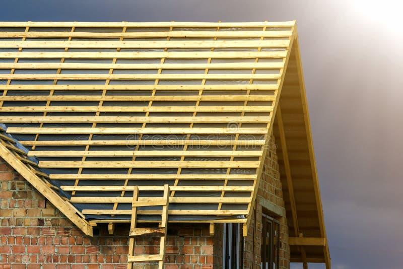 Detalle del primer del nuevo top de la casa del ladrillo con dos ventanas plásticas estrechas del ático y del bastidor de madera  fotos de archivo libres de regalías
