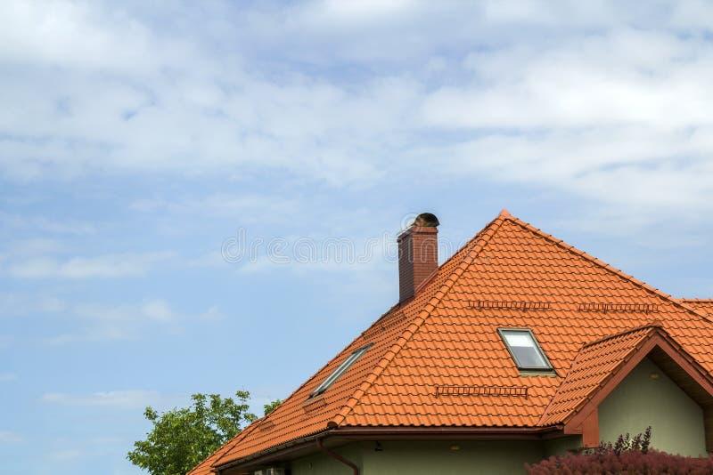 Detalle del primer del nuevo top moderno de la casa con el tejado rojo escalonado, alta chimenea, ventanas del ático en backgroun fotos de archivo