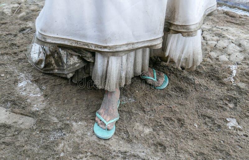 Detalle del vestido de boda blanco sucio y del pie asqueroso cubiertos por el fango y la suciedad fotografía de archivo