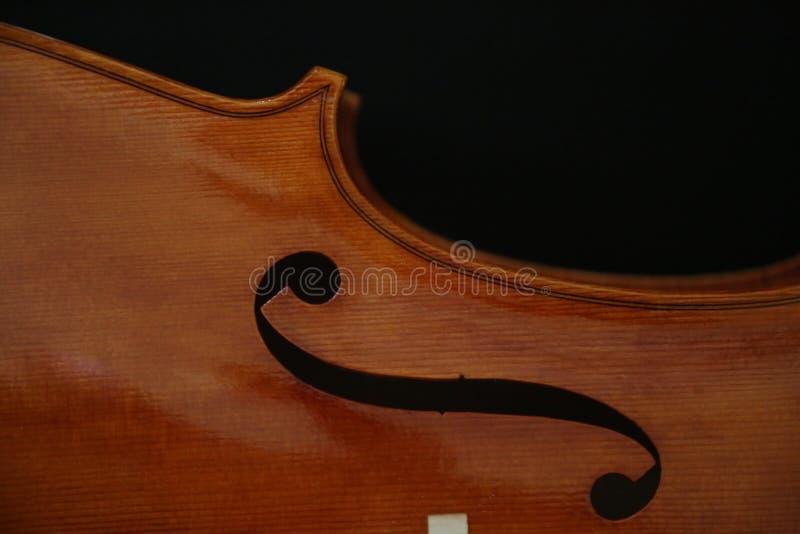 Detalle del violín con el detalle de f aislado en negro fotos de archivo