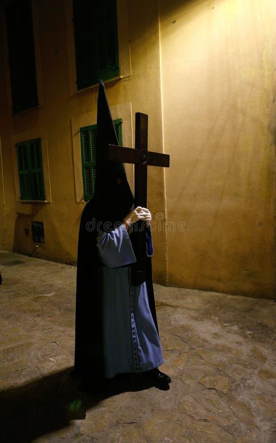 Detalle en un penitente encapuchado llevando una cruz durante una procesión de la semana santa de pascua en el detalle de Mallor imágenes de archivo libres de regalías