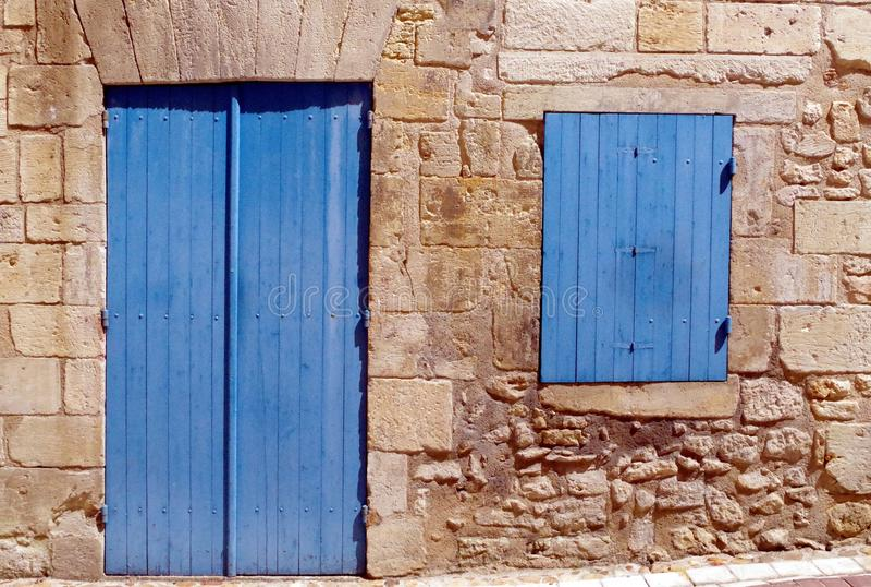 Detalle exterior de una casa de piedra tradicional con la ventana y la puerta azules cerradas foto de archivo