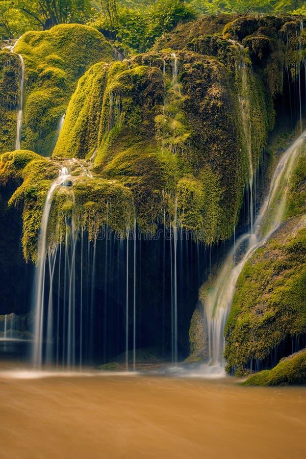 Detalle hermoso de una cascada que fluye sobre una roca cubierta musgo con una cueva debajo imagenes de archivo