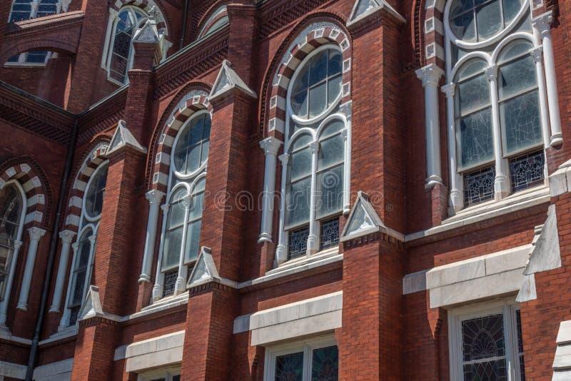 Detalle la arquitectura exterior de la iglesia g?tica del renacimiento del ladrillo rojo con las ventanas arqueadas imagen de archivo libre de regalías