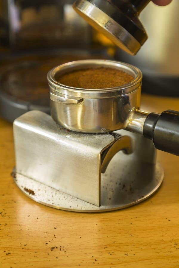 Detalle la imagen después de apisonar los argumentos del café express en una bayoneta imagenes de archivo