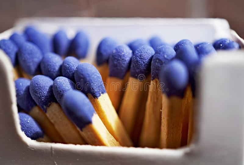 Detalle macro de los palillos del partido de seguridad con las cabezas azules en la caja del partido y el x28 de papel; matchbox& fotografía de archivo