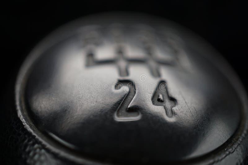 Detalle macro de un botón negro de un engranaje manual usado del cambio (palillo de engranaje) en el vehículo envejecido foto de archivo libre de regalías
