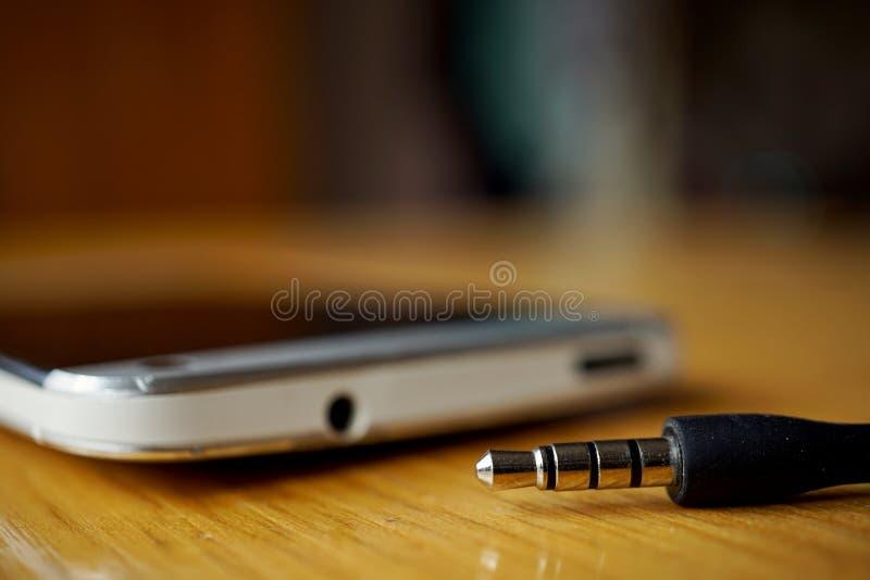 Detalle macro de un conector de auriculares del metal cerca el conector en el teléfono móvil, en la superficie de madera imagen de archivo libre de regalías