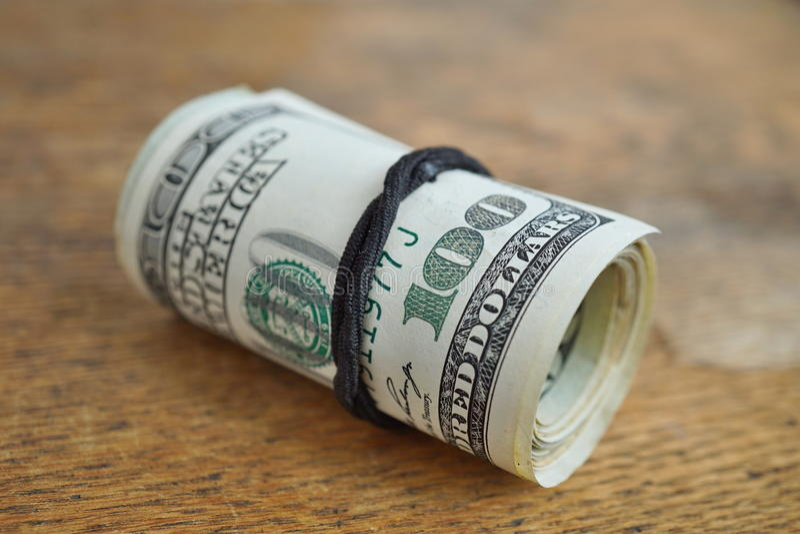 Detalle macro de un rollo verde de la moneda americana USD, dólares americanos con 100 dólares de billete de banco en el exterior imagenes de archivo