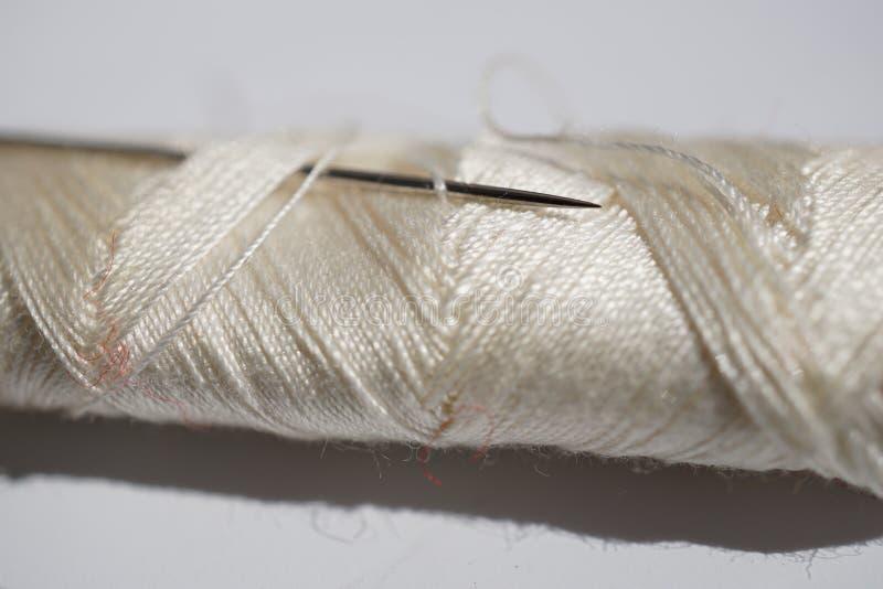 Detalle macro de una aguja aguda de plata insertada en el carrete del hilo blanco fotografía de archivo