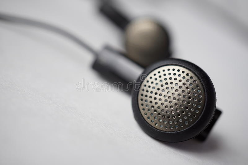 Detalle macro de una plata y de auriculares perforados negros (botones de oído) con los cables imágenes de archivo libres de regalías