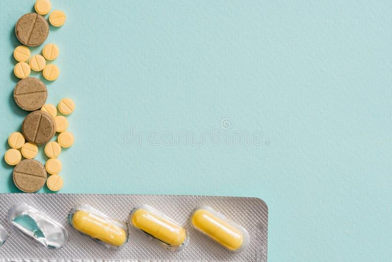 Detalle macro del tiro de las píldoras ovales amarillas de la tableta con los paquetes de ampolla en el fondo blanco con el espac fotos de archivo libres de regalías