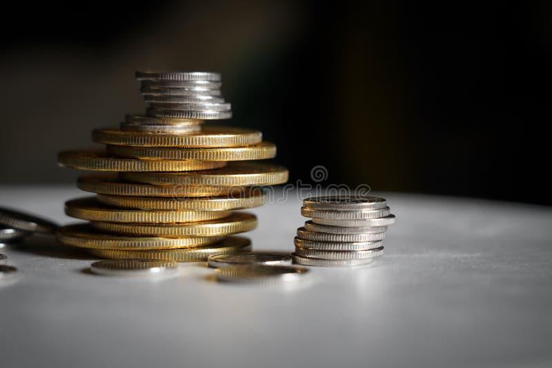 Detalle macro del tiro de las pilas de oro y color platas de la moneda en fondo oscuro con el espacio de la copia para el texto E fotos de archivo