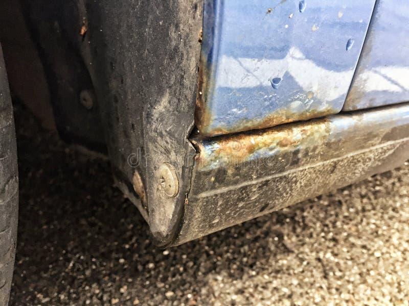 Detalle oxidado de la defensa y umbral del coche azul fotografía de archivo libre de regalías