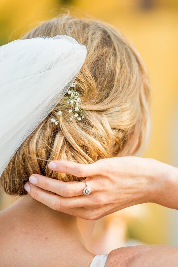 Detalle sincero de la novia hermosa con su mano que fija su pelo que muestra el anillo de compromiso fotografía de archivo libre de regalías