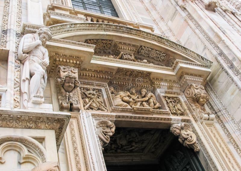 Detalles, bajorrelieves y esculturas arquitectónicos hermosos de la entrada a Milan Cathedral Duomo di Milano Italia foto de archivo libre de regalías