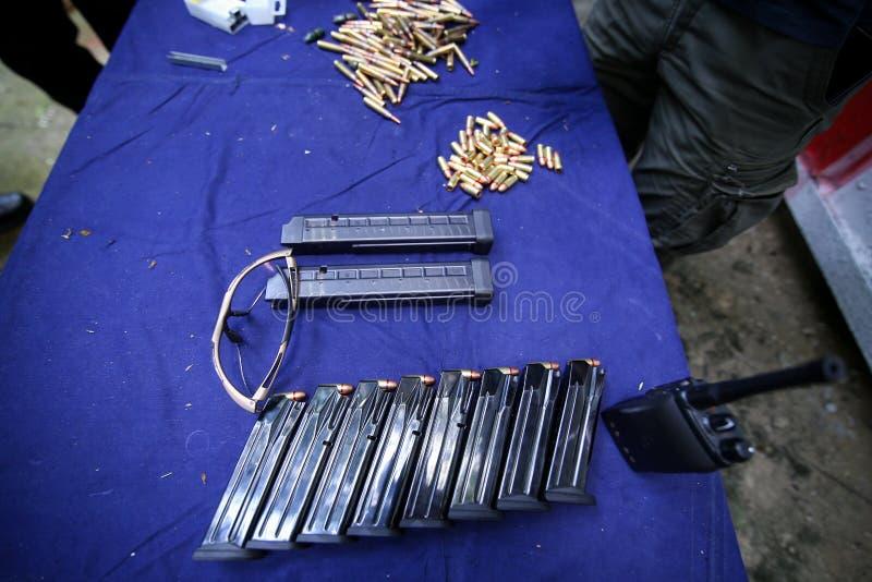 Detalles con los clips del arma, la munición de 9m m y los vidrios protectores en una tabla en una radio de tiro foto de archivo libre de regalías