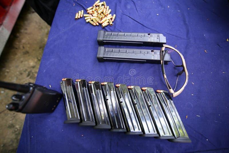 Detalles con los clips del arma, la munición de 9m m y los vidrios protectores en una tabla en una radio de tiro fotografía de archivo libre de regalías