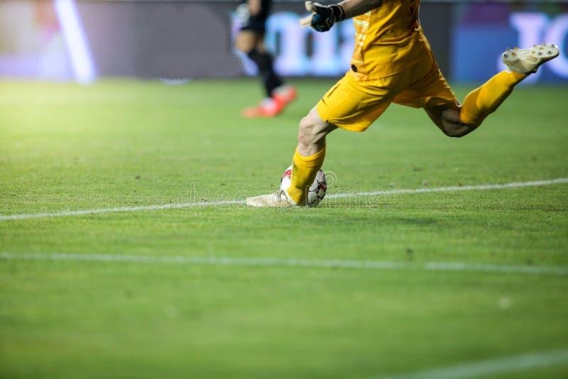 Detalles con los pies de un portero del fútbol que golpea la bola con el pie durante un partido imagenes de archivo