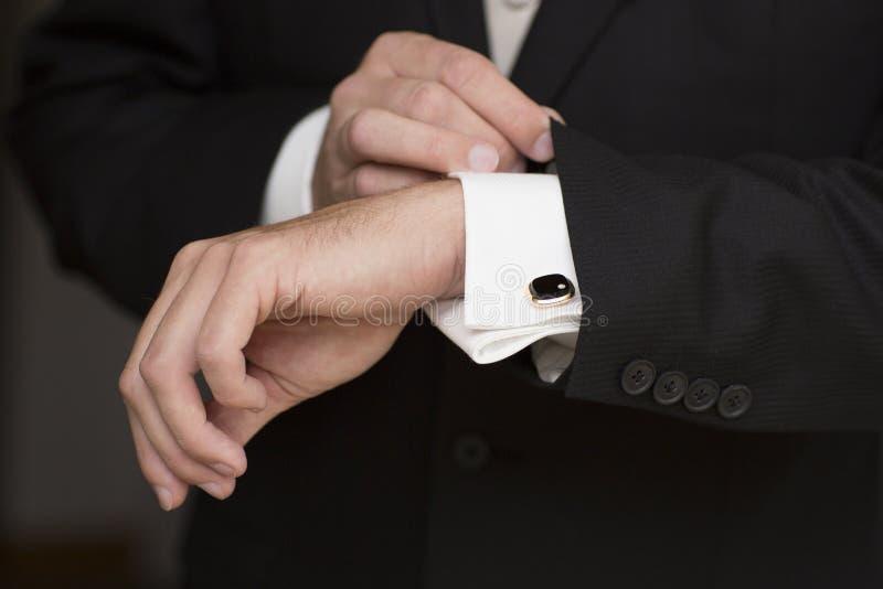 Detalles de la boda, mancuernas, traje masculino elegante y manos fotos de archivo libres de regalías