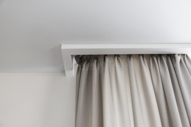 Detalles de las cortinas poner crema y del techo blanco fotos de archivo