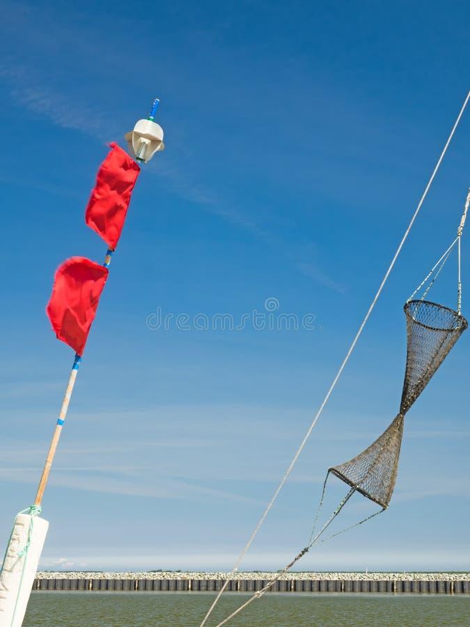 Detalles de un barco de pesca: boyas con las banderas rojas y la red de pesca fotos de archivo