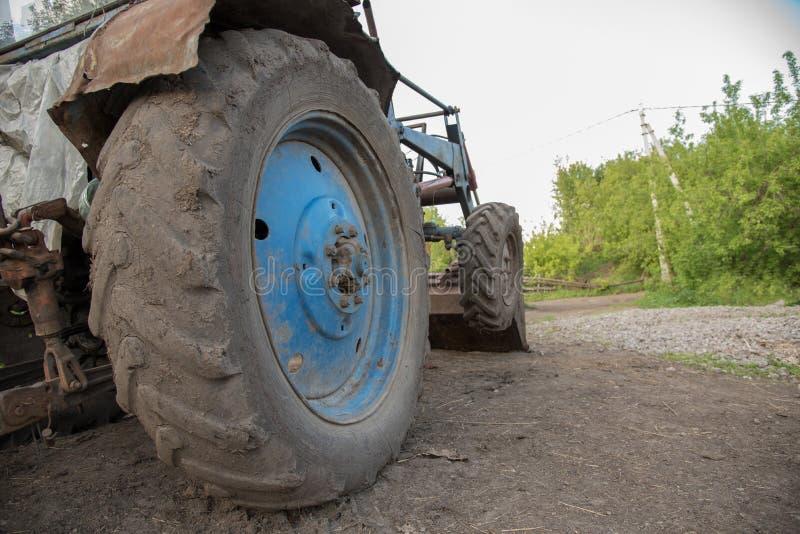 Detalles de un tractor azul con las ruedas sucias, motor, rud del pueblo imagen de archivo
