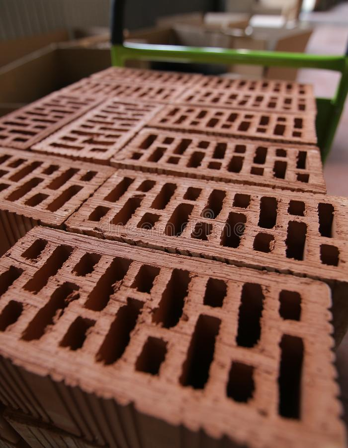 Detalles de una pila de ladrillos apilados de la arcilla con los agujeros imagenes de archivo