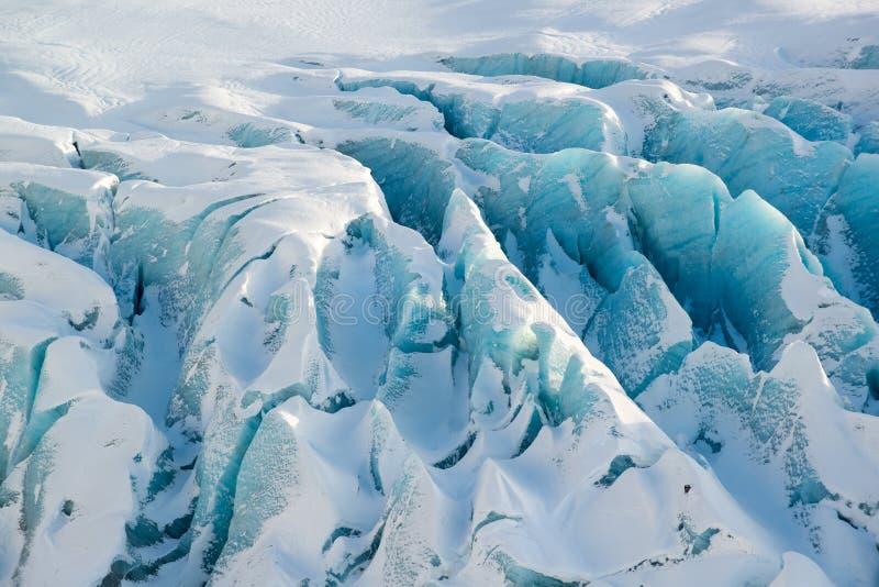 Detalles del glaciar Svinafellsjokull en el invierno, hielo texturizado vivo azul cubierto por la nieve, Islandia foto de archivo libre de regalías