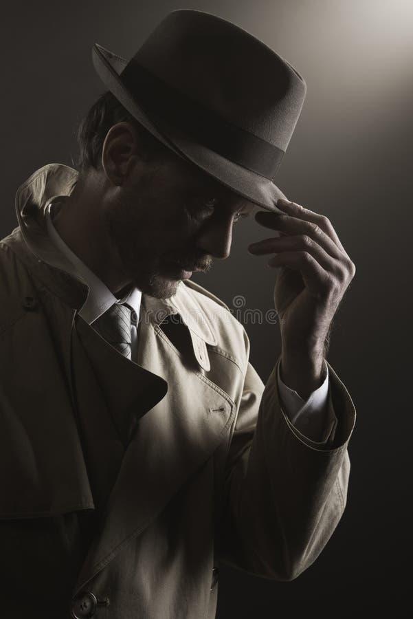 Detective adjusting his hat. Standing in the dark, film noir stock images