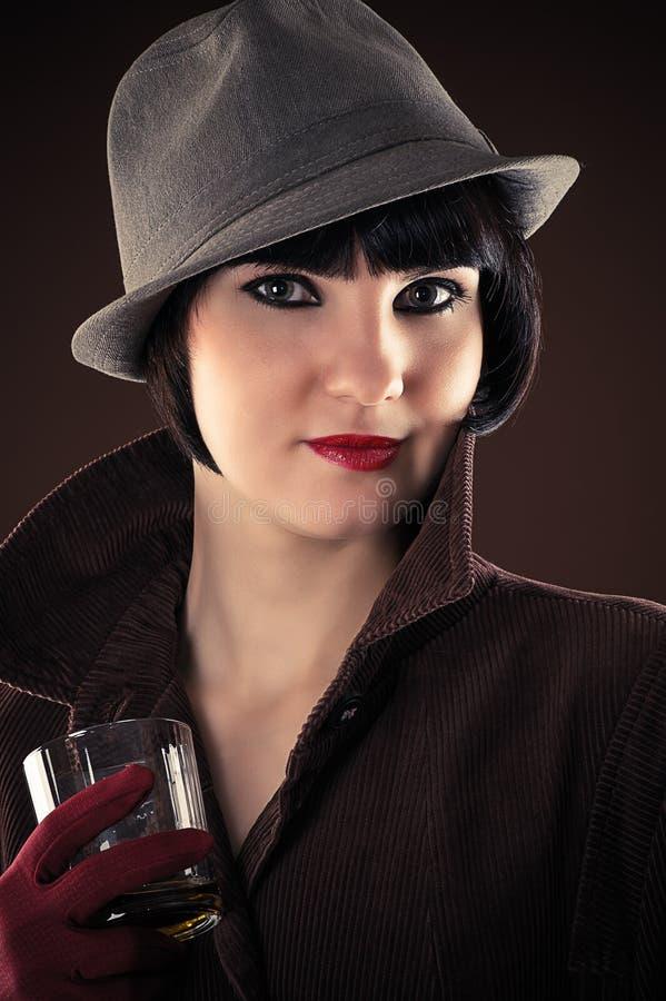 Detective de sexo femenino con un vidrio de whisky fotos de archivo